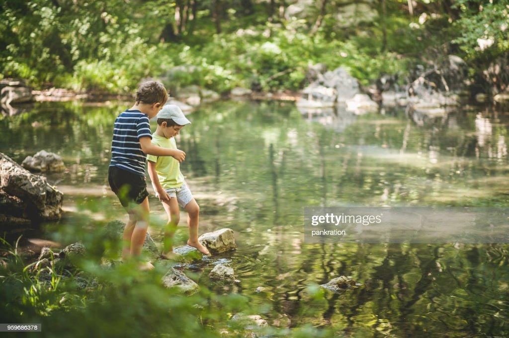 Jungs spielen neben dem See im Wald : Stock-Foto