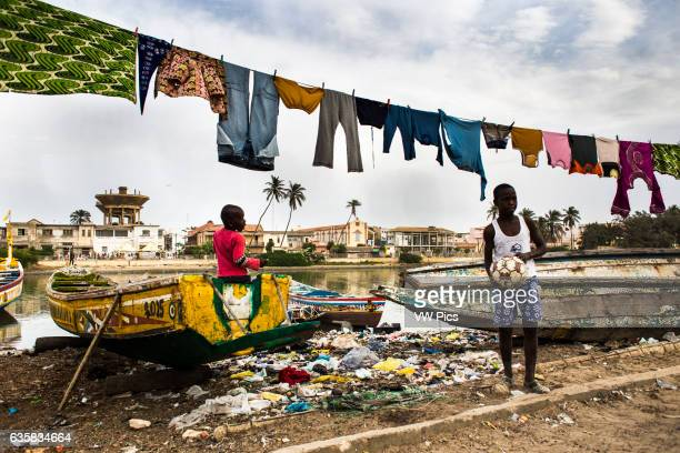 Boys playing next to the Senegal River in Saint Louis with clothes hanging
