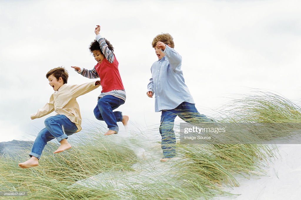 Boys playing on a dune : Stock Photo