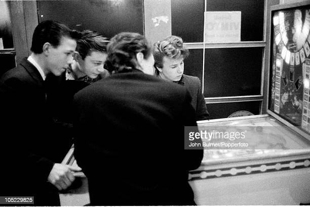 Boys playing on a pinball machine in the Black Country, West Midlands, January 1961.