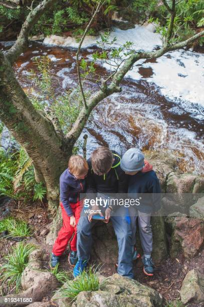 3 Boys playing on a smart phone in nature Near