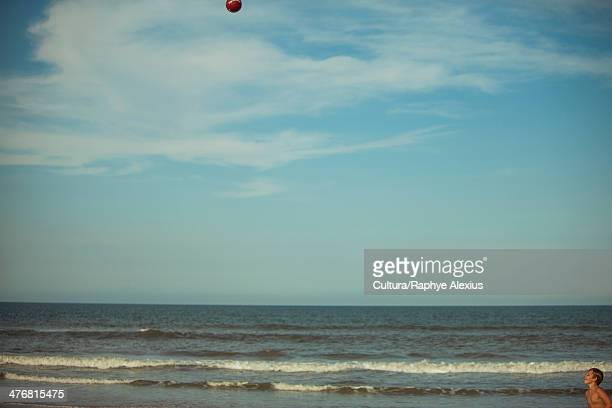 Boys playing on beach with ball