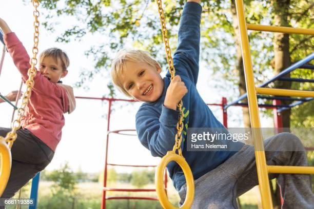 boys playing on monkey bars at playground - ジャングルジム ストックフォトと画像