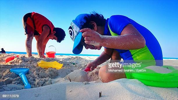 Boys Playing On Sand At Beach