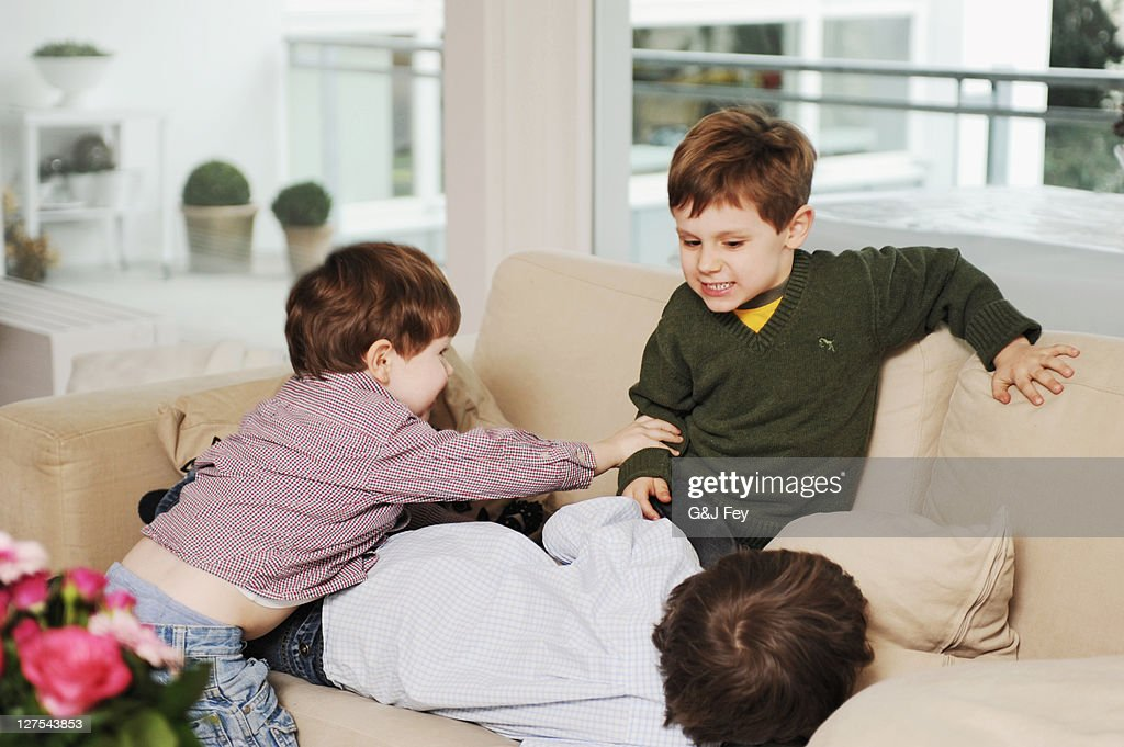 Boys playing on the sofa : Stock Photo