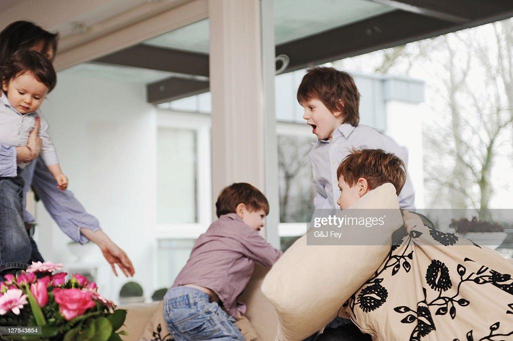 Boys playing on the sofa : Stock Photo