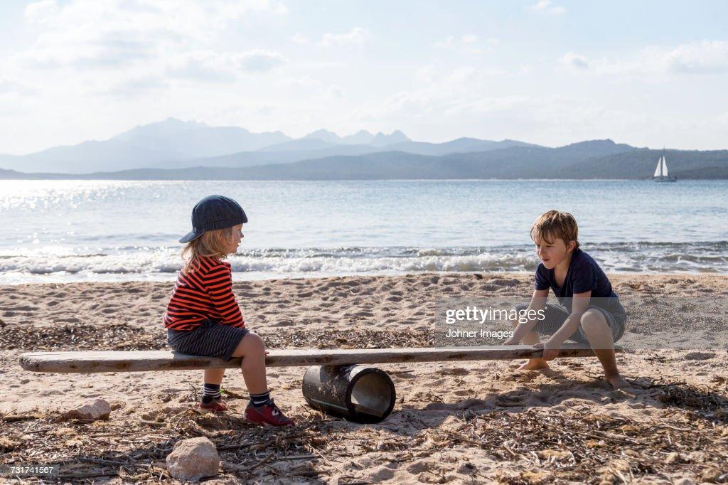 Boys playing seesaw on beach : Stock Photo
