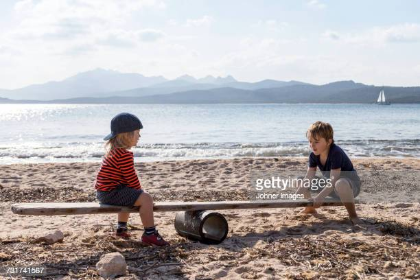 boys playing seesaw on beach - durability stock photos and pictures