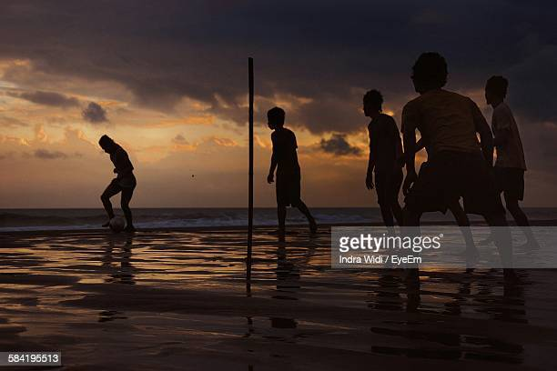 Boys Playing Soccer At Beach Against Sky During Sunset