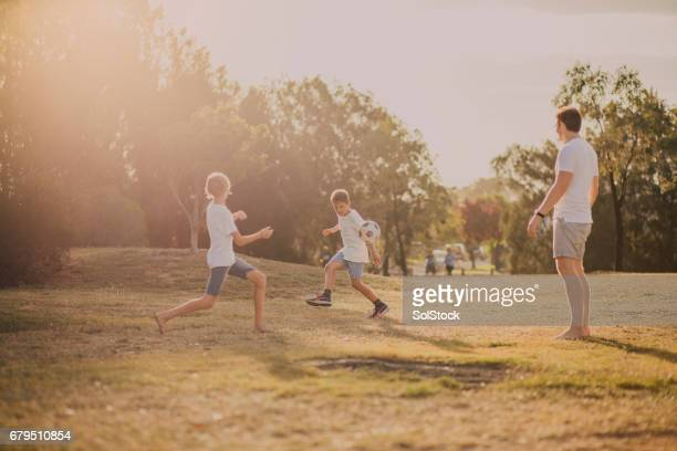 boys playing soccer in the park - public park stock photos and pictures
