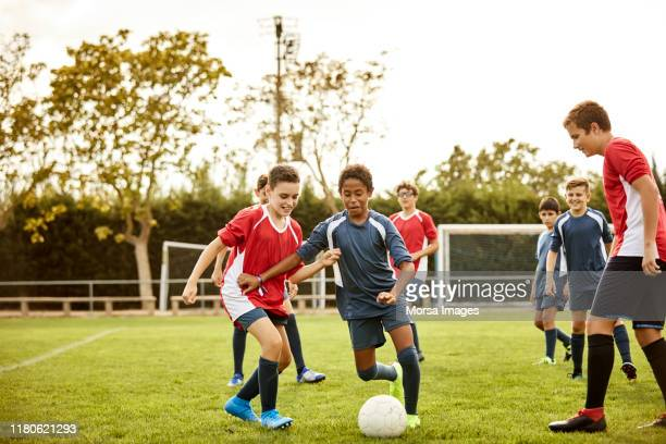 boys playing soccer match on training ground - childhood stock pictures, royalty-free photos & images