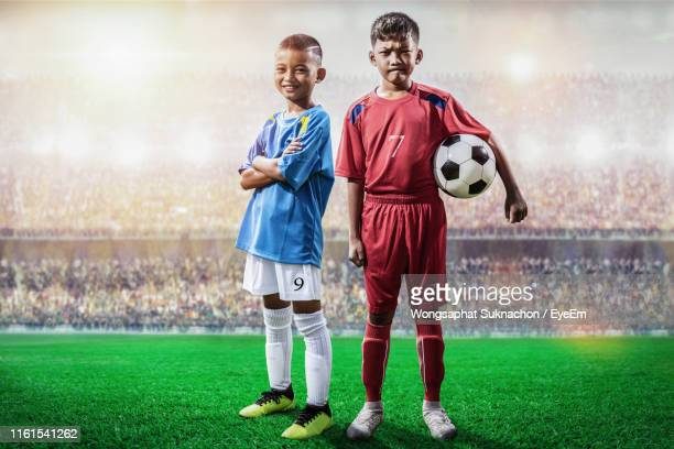 boys playing soccer on field - football strip stock pictures, royalty-free photos & images