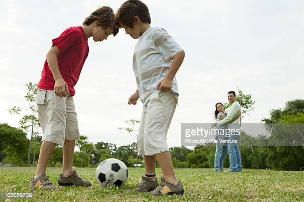 Boys playing soccer, parents embracing in background