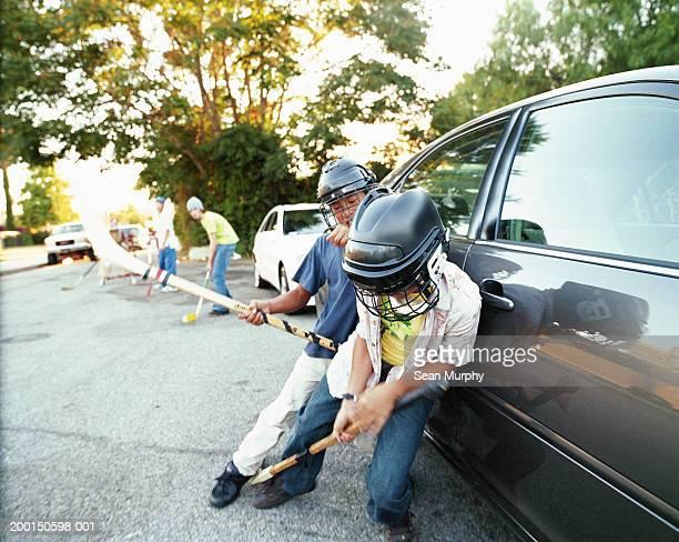 Boys (11-15) playing street hockey, leaning against car