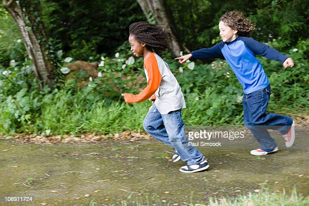 boys playing tag in the park - kids playing tag stock photos and pictures