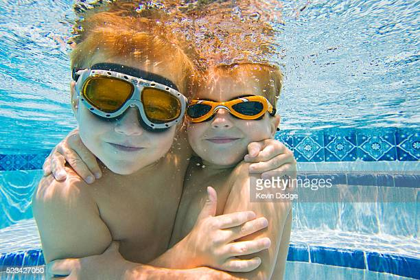 Boys Playing Underwater in Swimming Pool