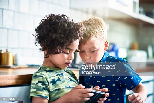 Boys playing video game in kitchen