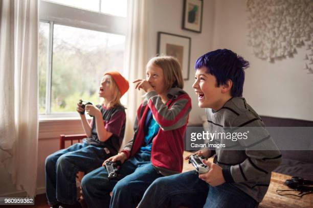Boys playing video game while sitting on bed at home