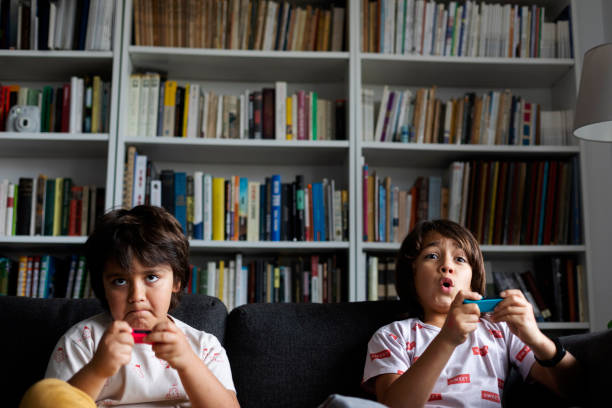 Boys playing video game while sitting on sofa against bookshelf in living room at home