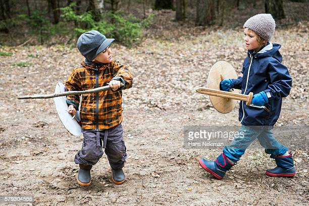 Boys playing warriors in the forest