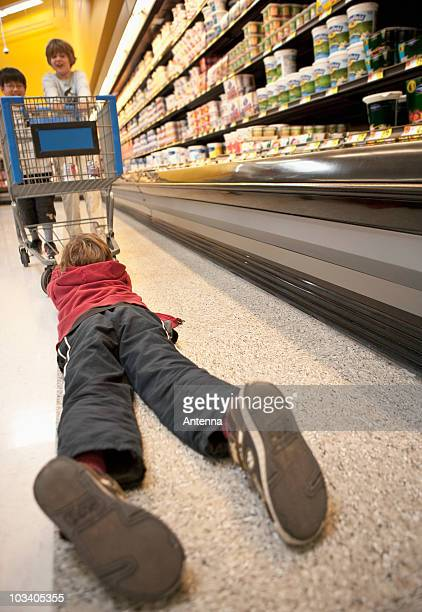 boys playing with a shopping trolley in a supermarket - dragging stock pictures, royalty-free photos & images