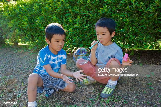 Boys playing with bubble wand, Machida, Tokyo Prefecture, Japan