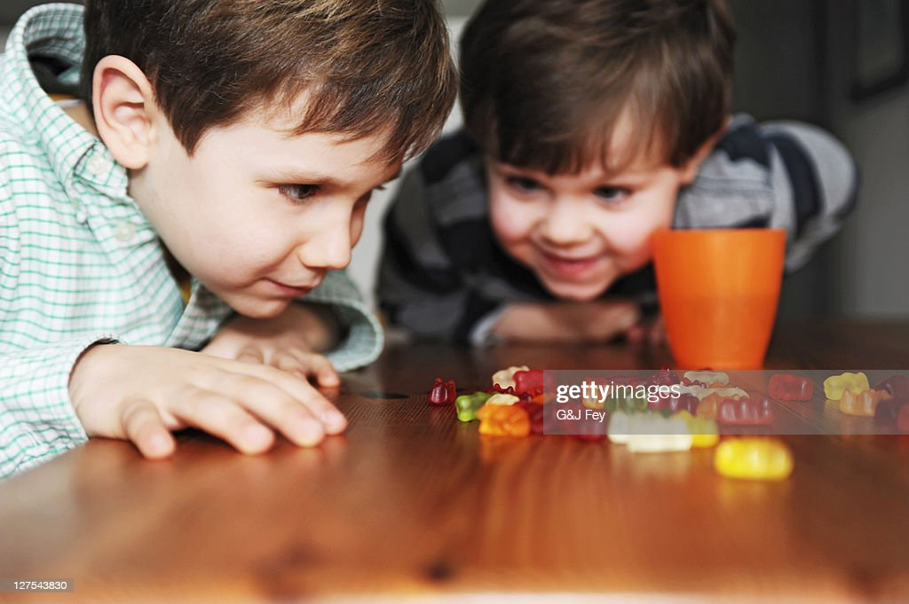 Boys playing with candy at table : Stock Photo
