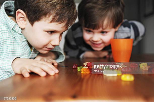 boys playing with candy at table - gummi bears stock photos and pictures