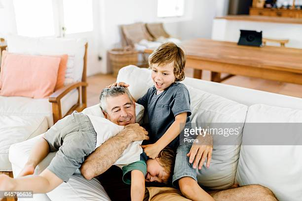 Boys playing with father lying on sofa at home