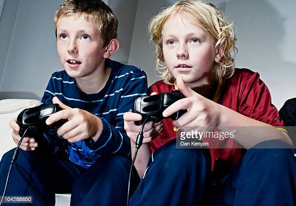 Boys playing with games consoles