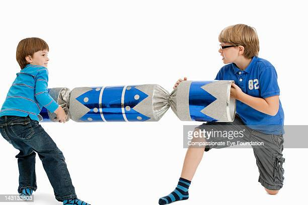"""boys playing with oversize cracker, studio shot - """"compassionate eye"""" stock pictures, royalty-free photos & images"""