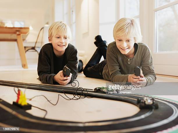 Boys playing with racetrack on the floor