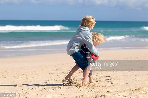 Niños jugando con bola de rojo en la playa