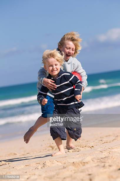 Boys playing with red ball on beach