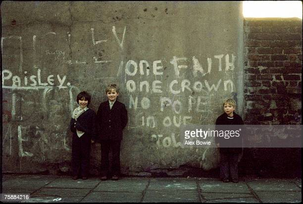 Boys pose beside some sectarian graffiti in the Protestant Shankill Road district of Belfast 21st March 1972