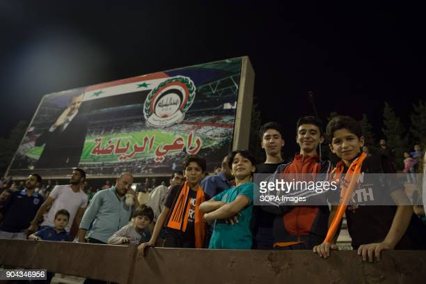 Boys pose in front of a billboard featuring Syrian President Bashar al Assad at the Syrian Football Cup final in Tishreen Stadium The Syrian football...