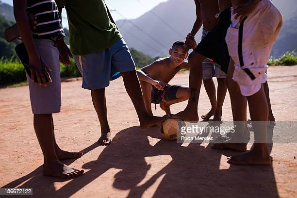 Boys pose while playing football in the Formiga favela or shantytown on November 2 2013 in Rio de Janeiro Brazil The favela was previously controlled...