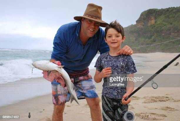 A Boys poses with his Father with his Fish