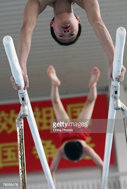 Boys practice on the parallel bars during their daily training at the Hubei Provincial Gymnastic Center on August 9 2007 in Wuhan of Hubei Province...