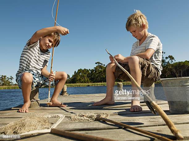 Boys preparing fishing rods for fishing