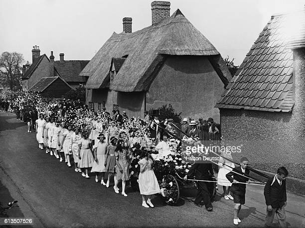 Boys pull the carriage holding the May Queen during the procession at the May festival in Elstow Green Bedford | Location Elstow Green Bedford...