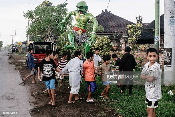 Boys puts the Ogoh-ogohs statue near the temple for procession before the afternoon parade on March 11, 2013 in Tunjuk Village, Tabanan, Bali,...