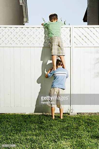 Boys Reaching over Fence into Neighbor's Yard