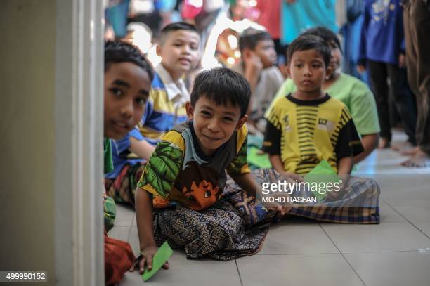 Boys react as they wait their turn to take part in a mass circumcision ceremony at a mosque in Ampang in the suburbs of Kuala Lumpur on December 5...