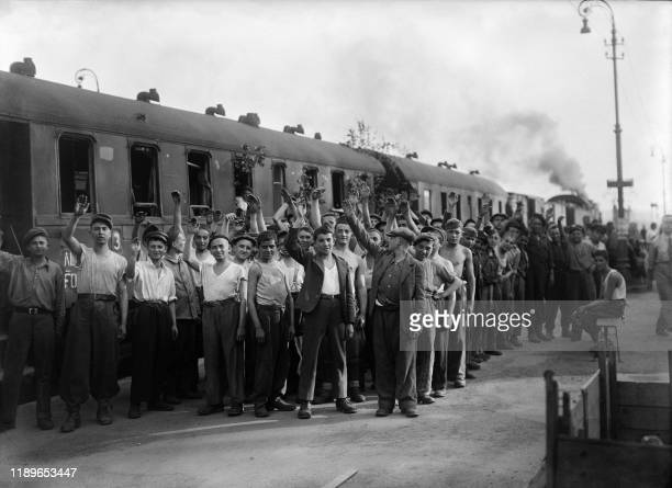 Boys repatriated from the German concentration camp of Buchenwald salute in front of the train that brought them back from Germany upon their arrival...