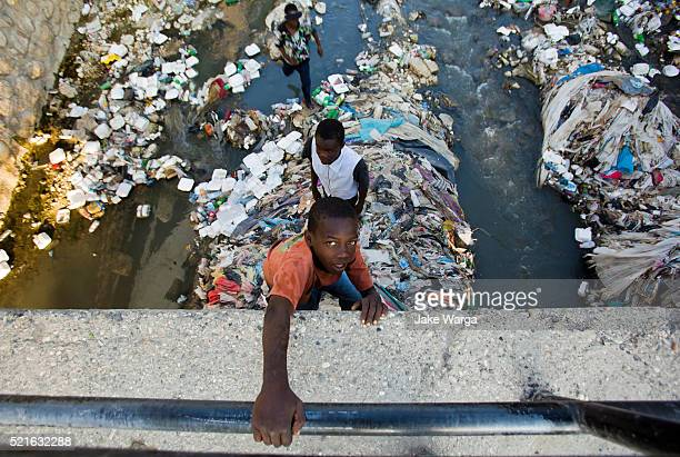 boys returning from scavenging in city river at port-au-prince - jake warga stock pictures, royalty-free photos & images