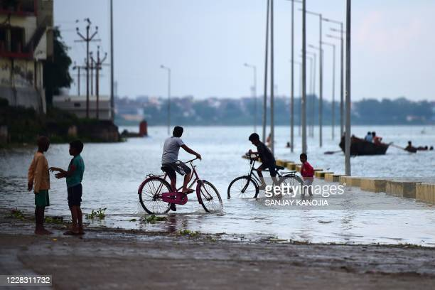 Boys ride bicycles along flooded road near the banks of the Ganges River following monsoon rainfalls in Allahabad on September 2, 2020.
