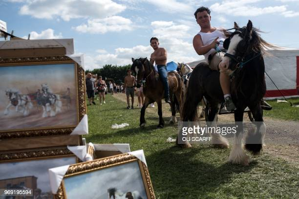Boys ride horses past trade stalls on the opening day of the annual Appleby Horse Fair in the town of ApplebyinWestmorland northwest England on June...