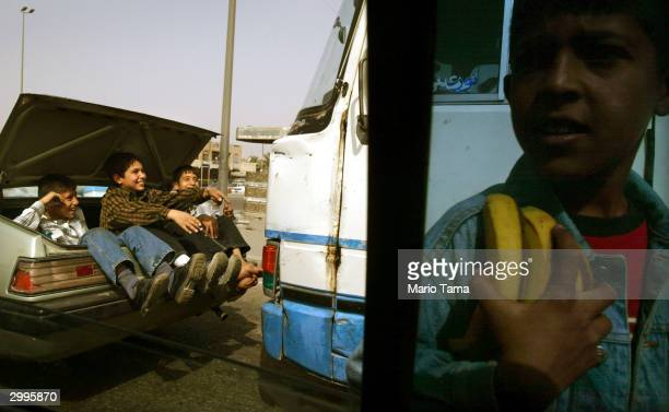 Boys ride in the trunk of a car as another sells bananas February 19 2004 in Baghdad Iraq US administrator Paul Bremer said today changes are...