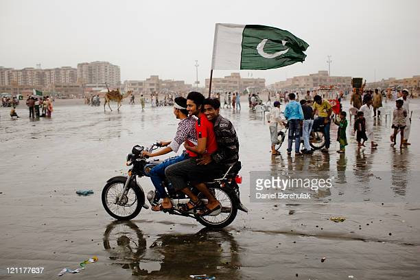 Boys ride on a motorbike as people gather at Seaview waterfront to celebrate Pakistan's Independence Day on August 14 2011 in Karachi Pakistan...